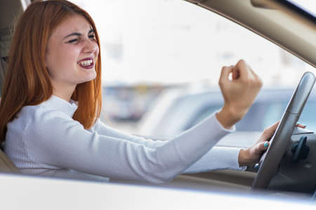 Closeup portrait of pissed off displeased angry aggressive woman driving a car shouting at someone with hand fist up. Negative human expression consept.
