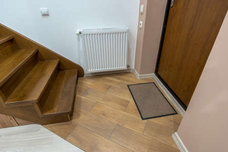 Interior of a house or appartment hallway with oak wooden stairs and room doors. Stock Photo