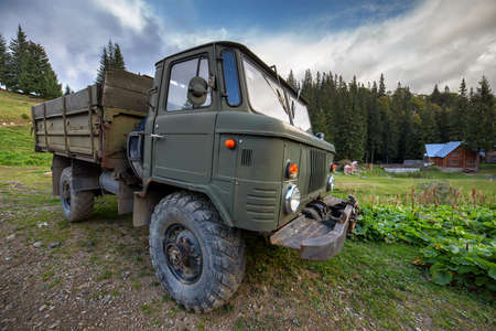 Old all terrain truck with big protector rubber tires for off road use. Stock Photo