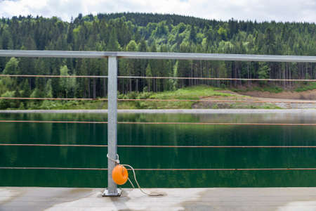 Yellow plastic buoy attached to a metal fence on the bank of a lake with green water. 写真素材