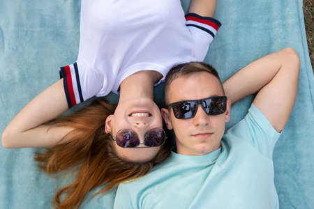 Young teenage couple in sunglasses laying together on blue cloth enjoying love relations.