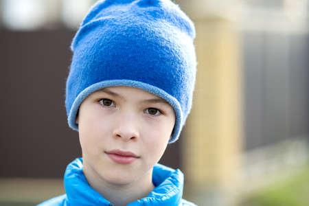 Chiuda sul ritratto del ragazzo sveglio del bambino in un berretto.