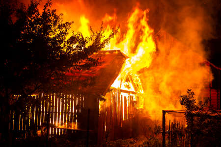 Wooden house or barn burning on fire at night. Stock fotó