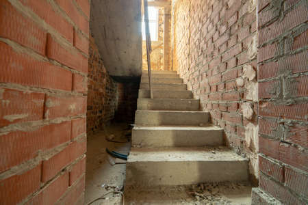 Interior of unfinished brick house with bare walls ready for plastering and concrete stairs prepared foe ceramic tiles cover.