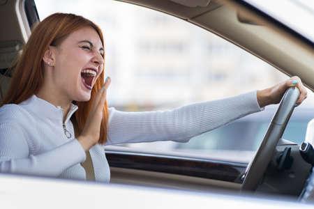 Close-upportret van pissige ontevreden boze agressieve vrouw die een auto drijft die bij iemand met omhoog handvuist schreeuwt. Negatieve menselijke expressie concept.