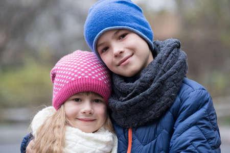 Due bambini ragazzo e ragazza che si abbracciano all'aperto indossando vestiti caldi nel freddo autunno o inverno.
