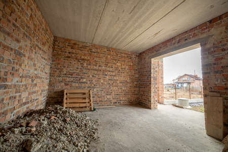 Interior of unfinished brick house with concrete floor and bare walls ready for plastering under construction. Real estate development Stockfoto
