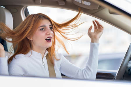 Closeup portrait of pissed off displeased angry aggressive woman driving a car shouting at someone. Negative human expression consept. Stockfoto