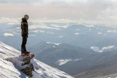Silhouette eines alleinstehenden Touristen, der auf einem schneebedeckten Berggipfel steht und an einem sonnigen Wintertag Aussicht und Leistung genießt. Abenteuer, Outdoor-Aktivitäten und gesundes Lifestyle-Konzept. Standard-Bild