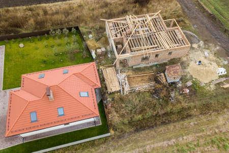 Luftaufnahme von oben nach unten von zwei Privathäusern, eines im Bau mit Holzdachrahmen und eines mit rotem Ziegeldach. Standard-Bild