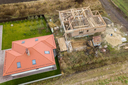 Top down aerial view of two private houses, one under construction with wooden roofing frame and another finished with red tiled roof. Archivio Fotografico