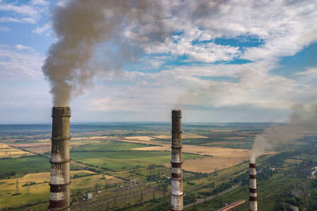 Aerial view of high chimney pipes with grey smoke from coal power plant. Production of electricity with fossil fuel. Reklamní fotografie