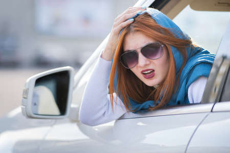 Young woman driving a car backwards. Girl with funny expression on her face while she made a fender bender damage to a rear vehicle.