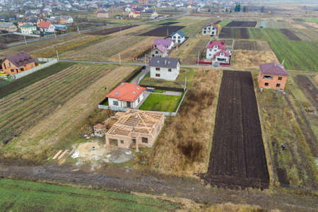 Top down aerial view of two private houses, one under construction with wooden roofing frame and another finished with red tiled roof. Zdjęcie Seryjne - 135567177