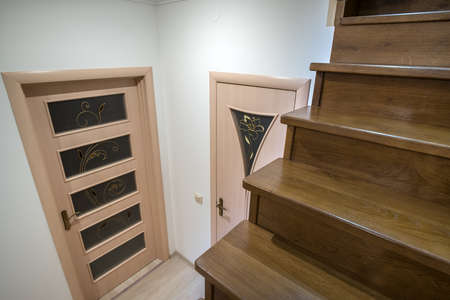 Interior of a house or appartment hallway with oak wooden stairs and room doors.