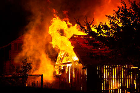 Casa de madera o granero ardiendo en llamas por la noche.