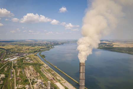 Aerial view of high chimney pipes with grey smoke from coal power plant. Production of electricity with fossil fuel. Archivio Fotografico