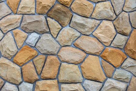 Superficie della parete astratta realizzata da pietre di sabbia per l'utilizzo come sfondo.
