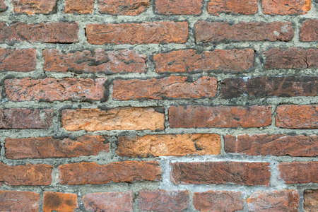 Weathered old red brick background with rough surface.
