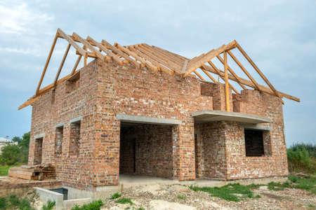 Chantier avec maison en brique inachevée avec charpente en bois pour futur toit en construction.