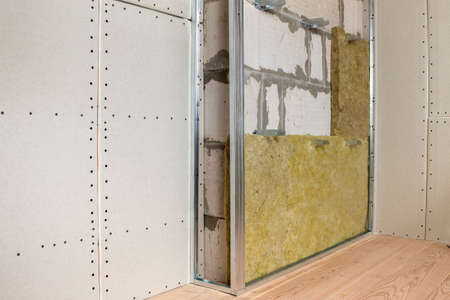 Wall of a room under renovation with mineral rock wool insulation and metal frame prepared for drywall plates.