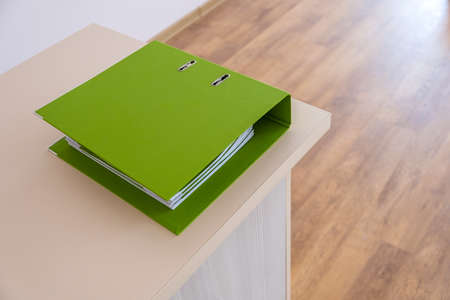 Green binder with office documents on a working table.