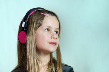 Pretty smiling cild girl listening to music in big pink earphones.