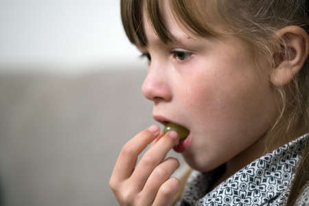Close-up portrait of happy little child girl with long hair licking her finger after eating something.