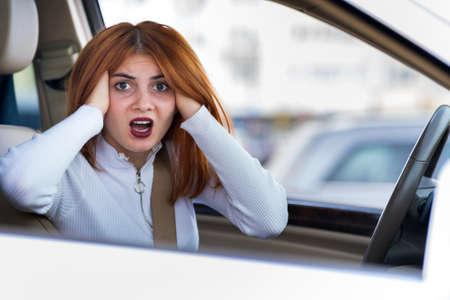 Ritratto del primo piano della donna aggressiva arrabbiata dispiaciuta incazzata che guida un'automobile che grida a qualcuno. Concetto negativo di espressione umana.