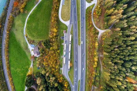 Top dawn aerial view of freeway speed road between yellow autumn forest trees in rural area. Stock Photo