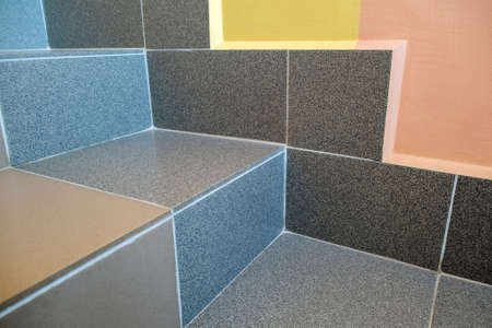 Wide staicase covered with ceramic tiles indoors in a house interior.