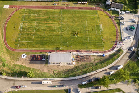 橄榄球场的鸟瞰图在用绿草盖的体育场的体育场在农村镇区域。