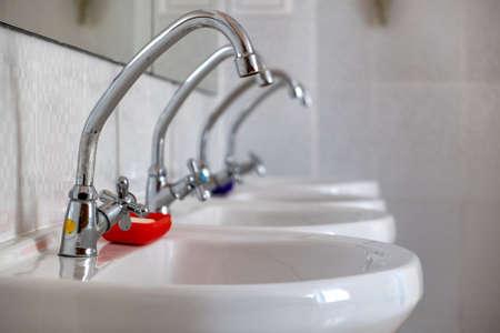 Weiße Keramikwaschbecken mit glänzendem Edelstahl-Wasserhahn. Standard-Bild