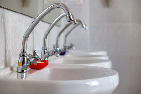 White ceramic washing basins with shiny stainless steel water tap. Stock Photo