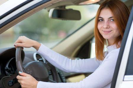 차를 운전하는 빨간 머리를 가진 젊은 여자.