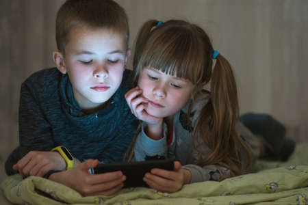 Two children brother and sister watching video on smartphone screen together.