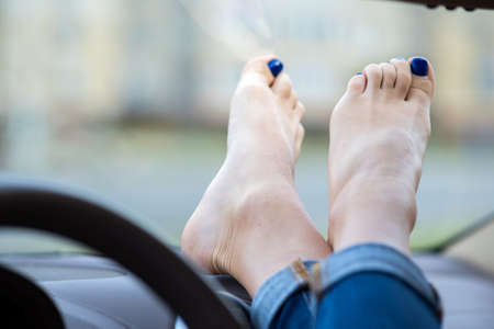 Close up of woman driver feet resting on car dashboard.