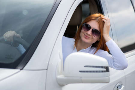 Young woman driver behind car steering wheel.