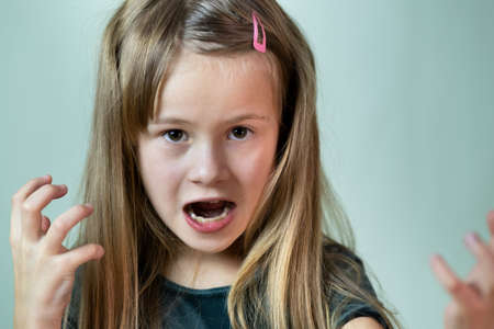 Close up portrait of angry shouting child girl looking aggressively in camera.