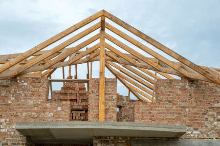 Building site with unfinished brick house with wooden roofing frame for future roof under construction. Zdjęcie Seryjne