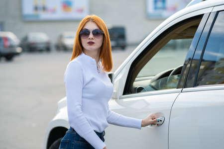 Yong ładna kobieta stojąca w pobliżu dużego samochodu terenowego na zewnątrz. Kierowca dziewczyna w ubranie poza swoim pojazdem. Zdjęcie Seryjne
