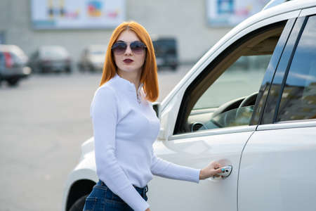 Yong pretty woman standing near a big all terrain car outdoors. Driver girl in casual clothes outside her vehicle. Stock Photo