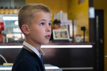Garçon enfant assis dans un restaurant de restauration rapide derrière une table vide en attente de nourriture.