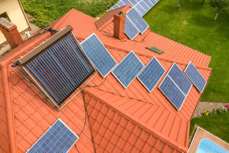 Aerial view of a new autonomous house with solar panels and water heating radiators on the roof. Stock Photo