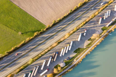 Top down aerial view of highway interstate road with fast moving traffic and parking lot with parked lorry trucks. 版權商用圖片