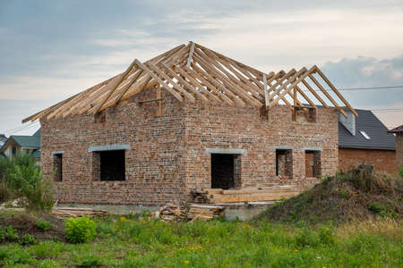 Building site with unfinished brick house with wooden roofing frame for future roof under construction.