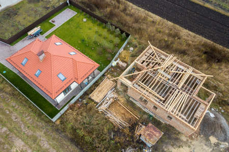 Top down aerial view of two private houses, one under construction with wooden roofing frame and another finished with red tiled roof. Zdjęcie Seryjne - 137001728