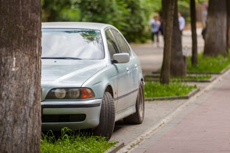 Car parked in pedestrian zone under trees along street with walking people on summer day.