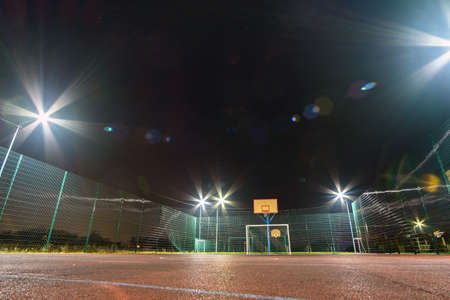 Outdoors mini football and basketball court with ball gate and basket surrounded with high protective fence brightly illuminated with spotlight lamps at night. Stock Photo
