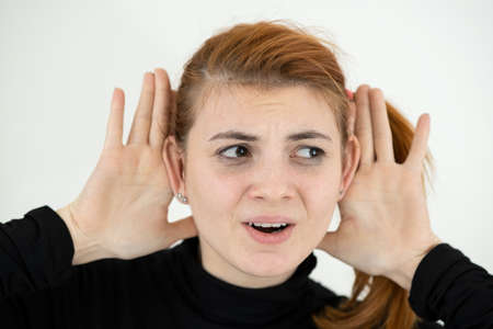 Close up portrait of funny girl holding her ears with hands like a monkey.
